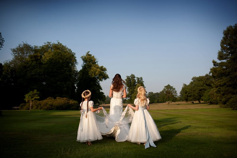 Bridebook.co.uk- flower girls carrying brides train
