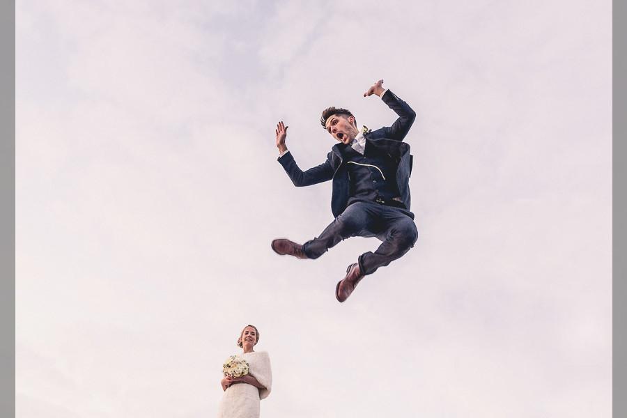 Bridebook.co.uk- groom jumping in the air as bride watches