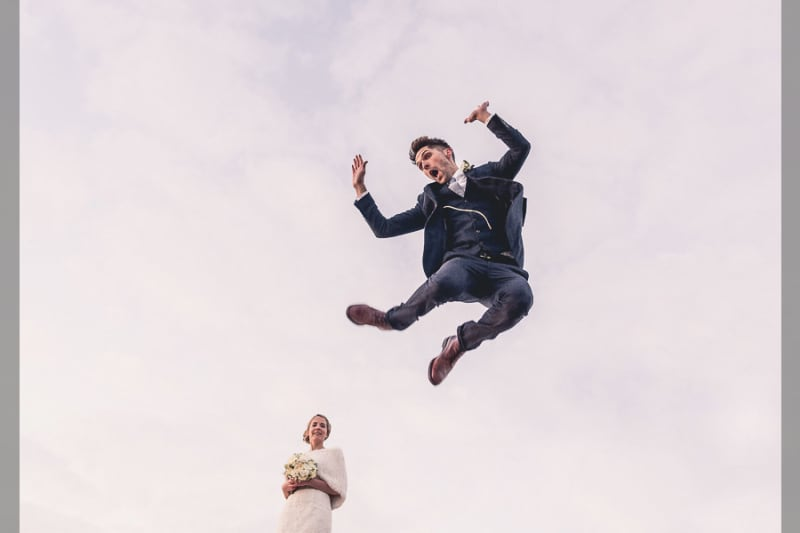 Bridebook.co.uk- groom jumping in the air as bride watches