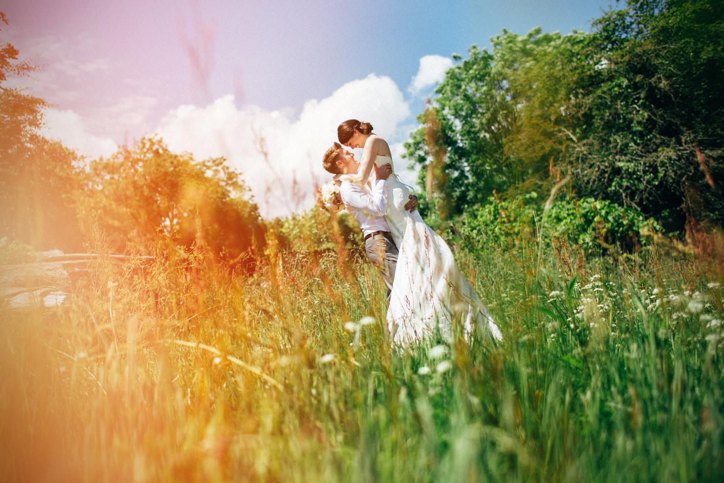 Bridebook.co.uk- groom lifting up bride in a field