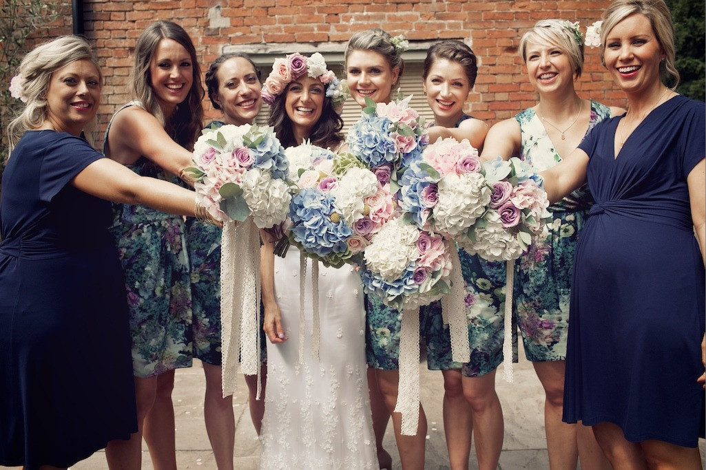 Bridebook.co.uk- bride and bridesmaids dressed in navy holding up bouquets