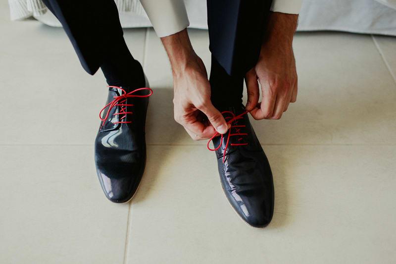 Bridebook.co.uk- groom tying red laces on black shoes