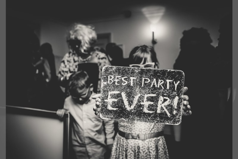 Bridebook.co.uk- girl holding up best party ever sign