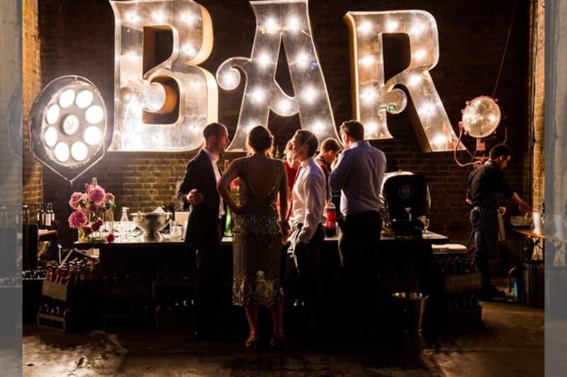 Bridebook.co.uk- wedding guests talking next to a big bar sign