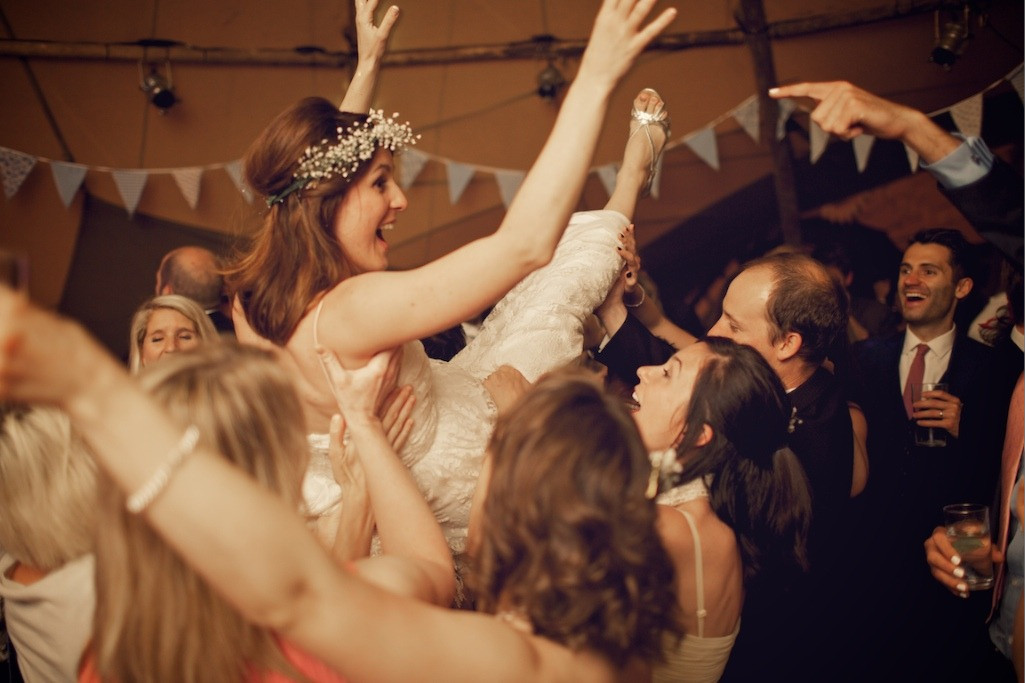 Bridebook.co.uk- bride being lifted up by the guests during reception