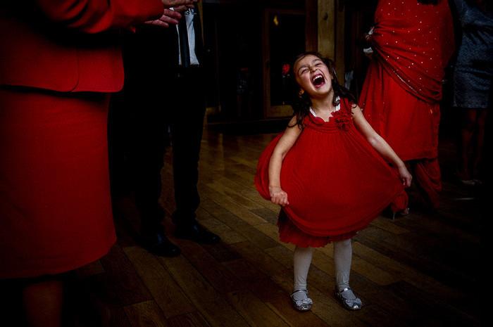 Bridebook.co.uk- flower girl dressed in red singing