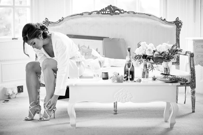 Bridebook.co.uk- bride putting on shoes in bridal suite