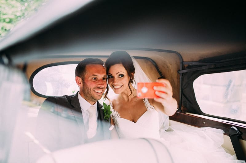 Bridebook.co.uk- bride and groom taking selfie at the back of wedding car