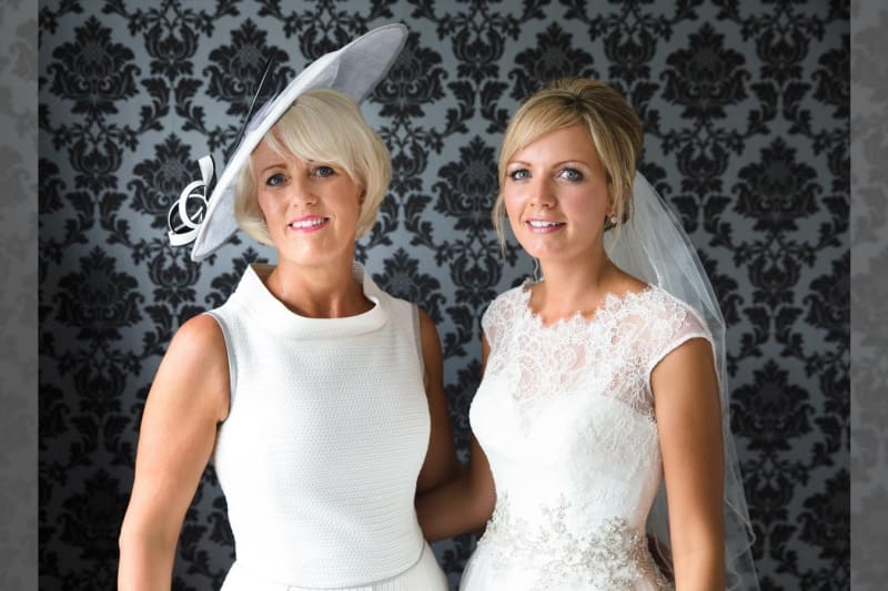 Bridebook.co.uk - Bride and mother both in white smiling at the camera