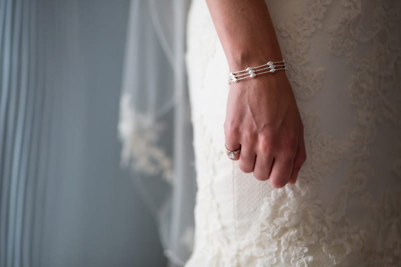 Bridebook.co.uk- bride wearing a ring and a pearl bracelet