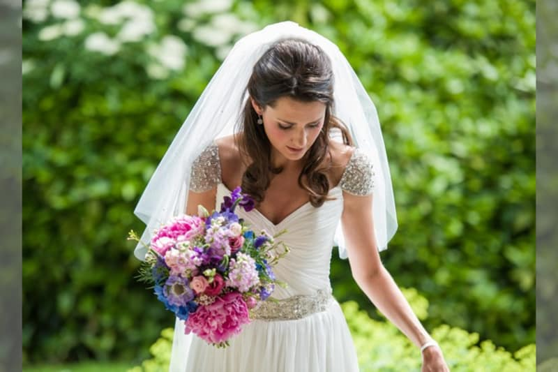 Bridebook.co.uk- bride in an embellished dress holding her bouquet