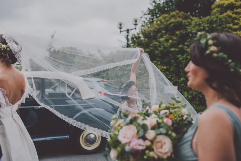 Bridebook.co.uk- brides cathedral length veil being adjusted by bridesmaid