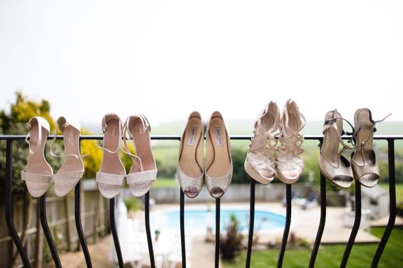 Bridebook.co.uk- bride and bridesmaid shoes balanced on a balcony rail