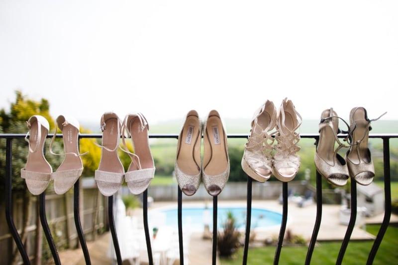 Bridebook.co.uk- bride and bridesmaid shoes balanced on a balcony rail