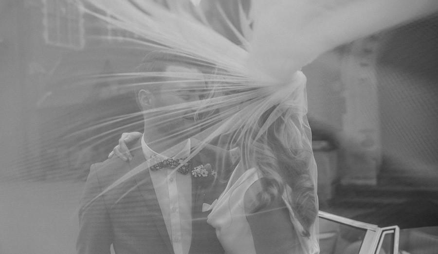 Bridebook.co.uk- bride and groom behind brides billowing veil