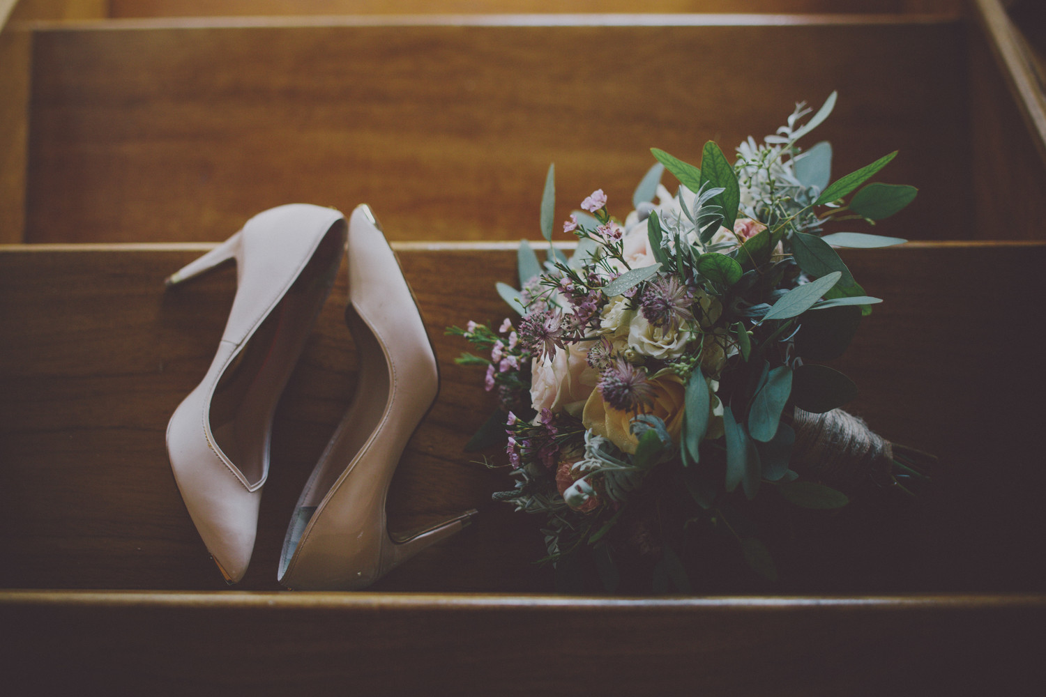 Bridebook.co.uk- wedding shoes and bouquet lying on stairs