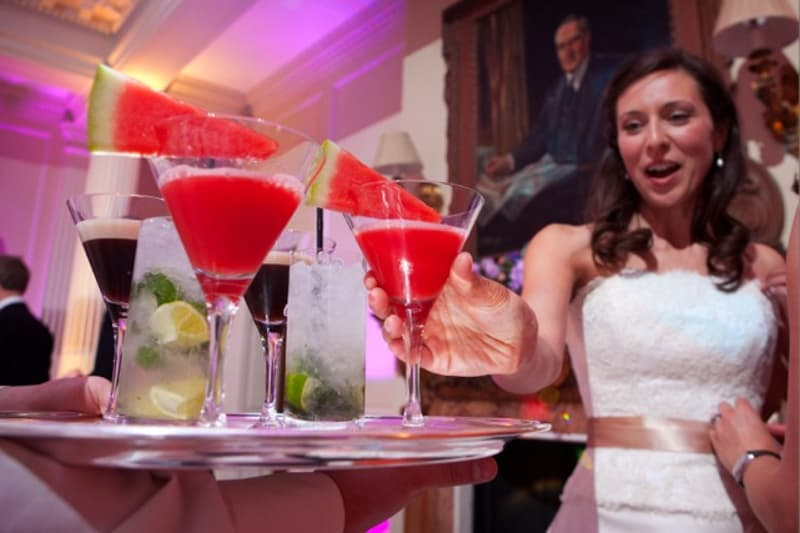 Bridebook.co.uk- bride reaching for a watermelon cocktail