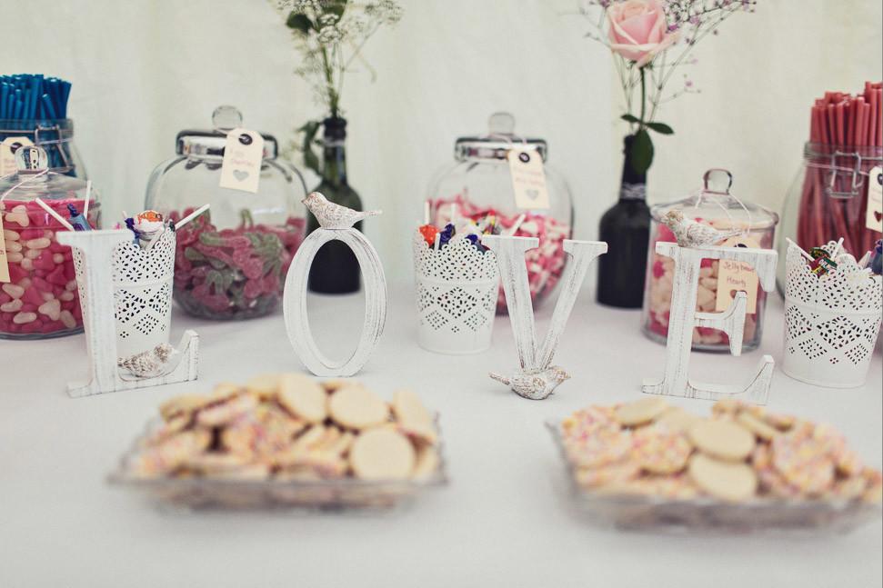 Bridebook.co.uk- love sign in front of desert table