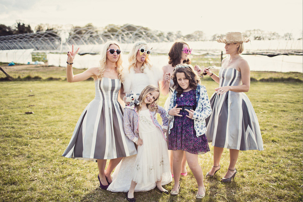 Bridebook.co.uk- bride bridesmaids and flower girl posing with props