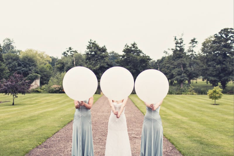 Bridebook.co.uk- bride and bridesmaids holding big white baloons