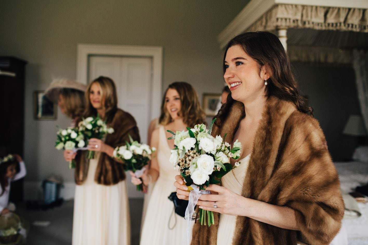 Bridebook.co.uk- bridesmaids in matching dresses and faux fur covers