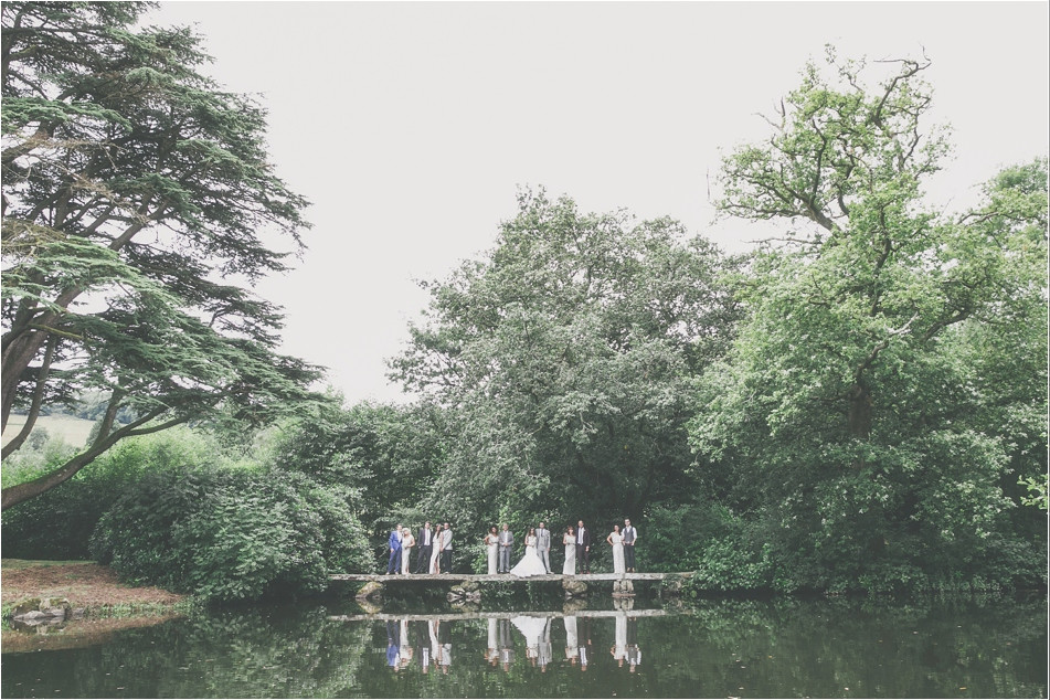 Bridebook.co.uk- bridal party standing on a bridge reflected in water