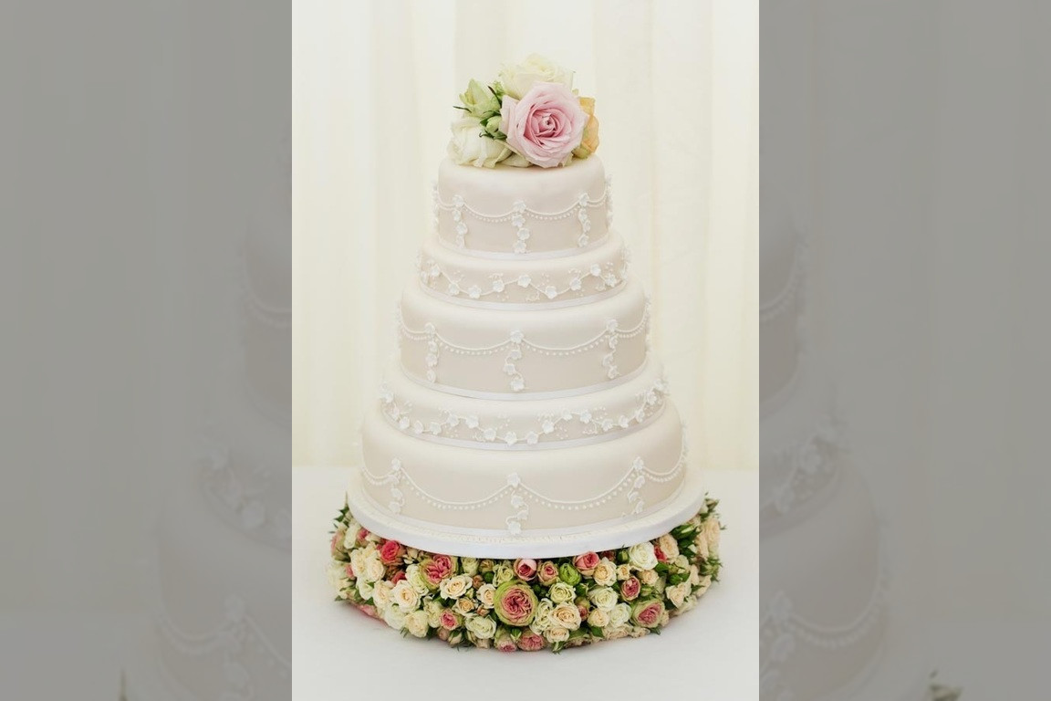 Bridebook.co.uk- five tier white wedding cake topped up with roses