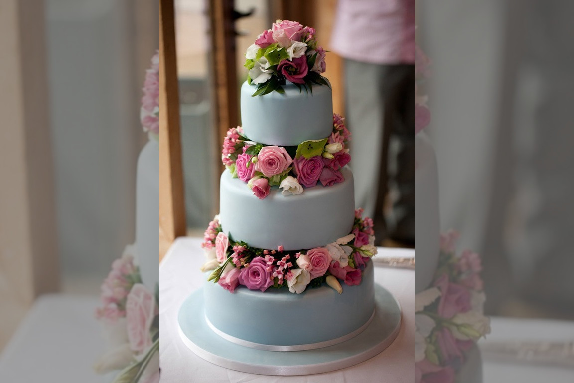 Bridebook.co.uk- three layer pale blue cake decorated with pink roses and lilies