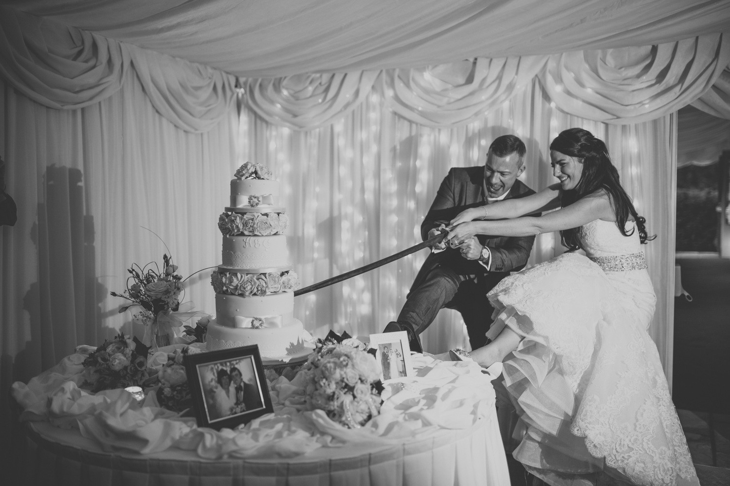 Bridebook.co.uk- bride and groom having fun cutting the cake with a ceremonial sword