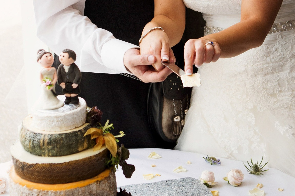 Bridebook.co.uk- bride and groom cutting their cheese cake