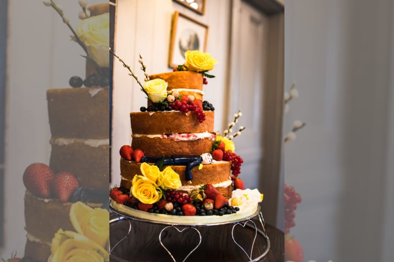 Bridebook.co.uk- naked cake decorated with yellow roses and berries