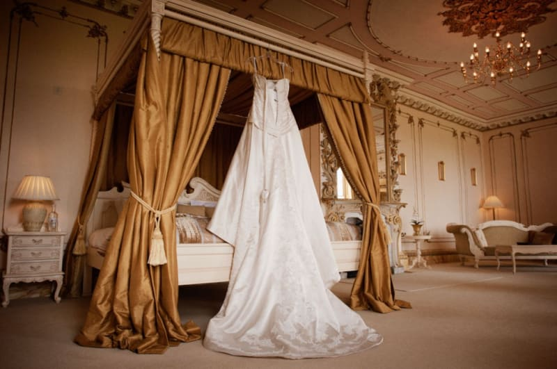Bridebook.co.uk- wedding dress hanging up above the bed in the bridal suite
