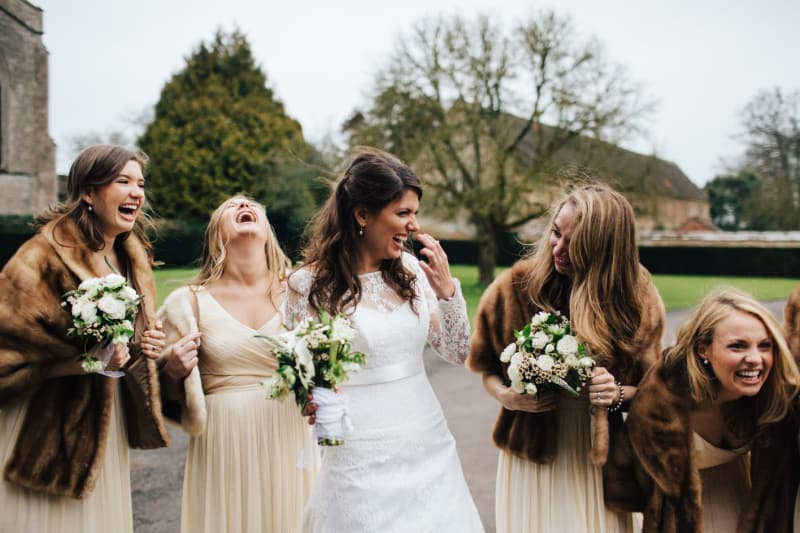 Bridebook.co.uk- brides and bridesmaids dressed in faux fur covers lauhing