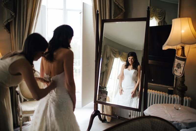 Bridebook.co.uk- bride getting ready while smiling at herself in the mirror