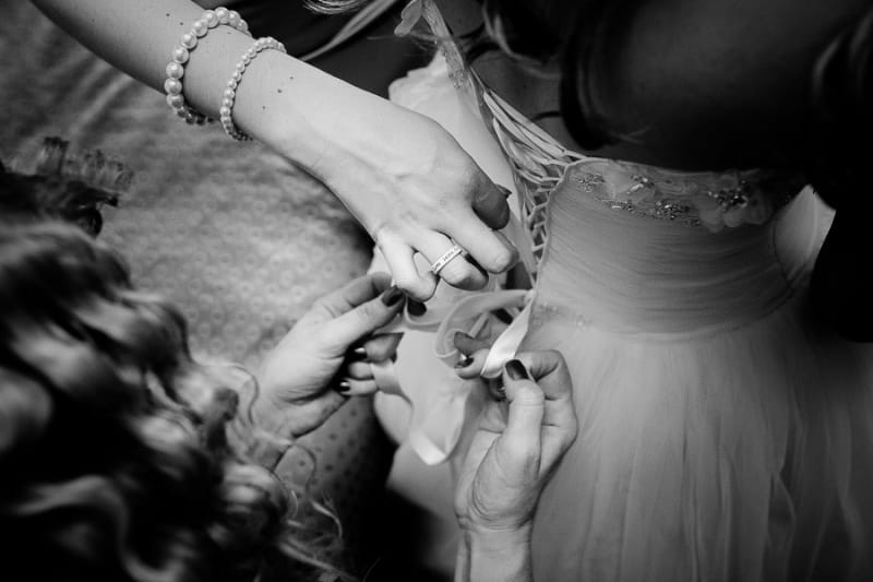 Bridebook.co.uk- bride being laced into her dress