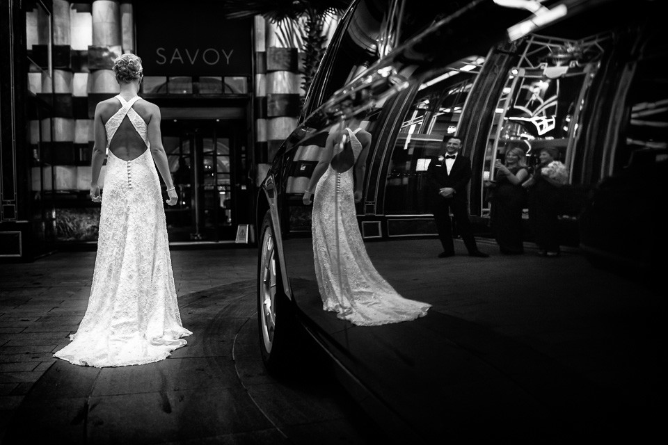 bridebook.co.uk bride with long train black and white next to car