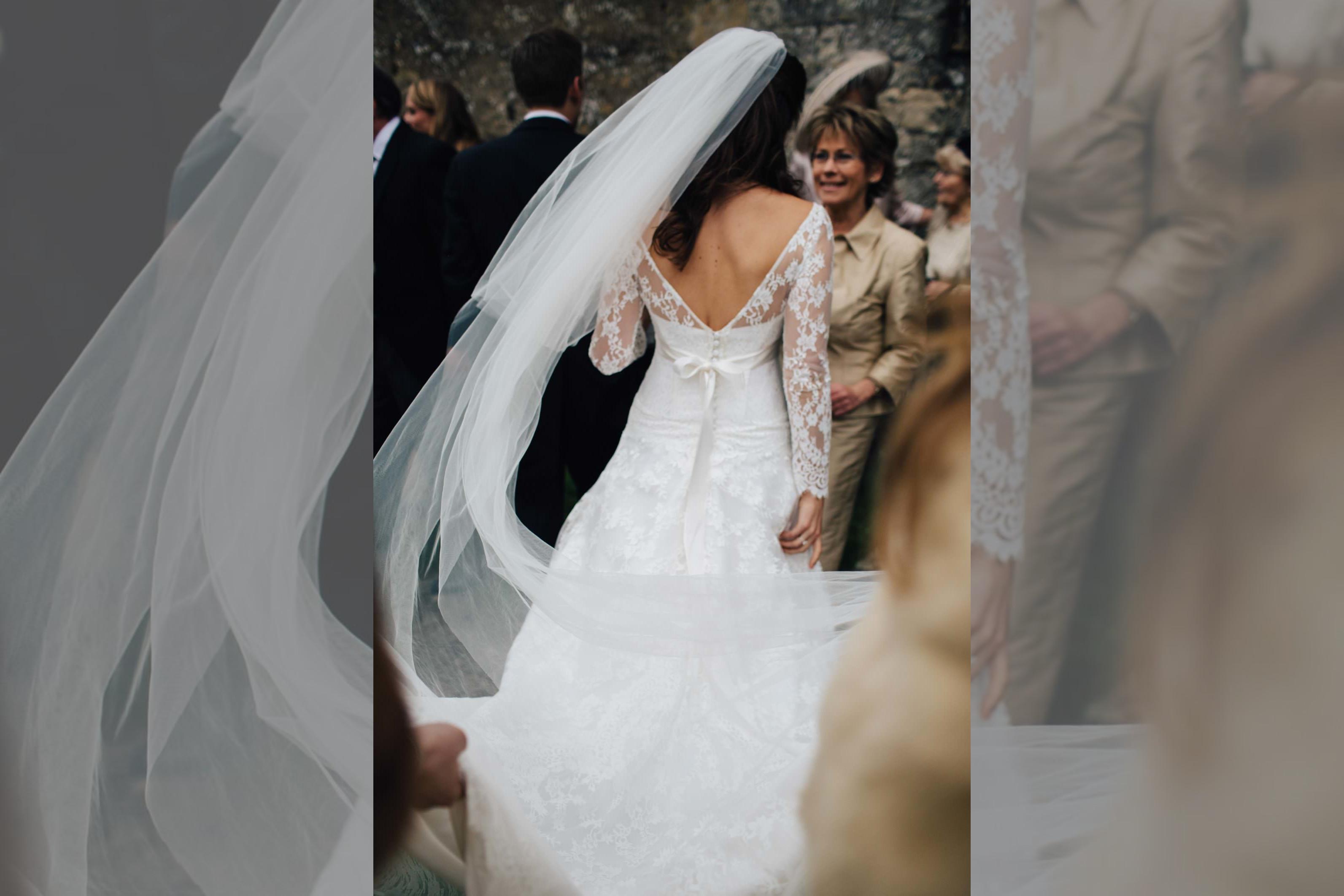 Bridebook.co.uk- bride with veil trailing behind her