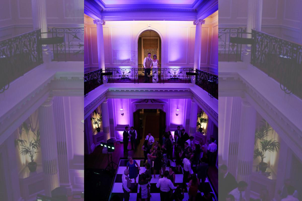 Bridebook.co.uk- bride and groom looking down at guests dancing