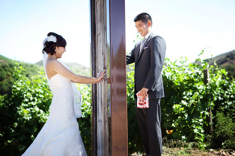 Bridebook.co.uk- bride and groom on different side of the door