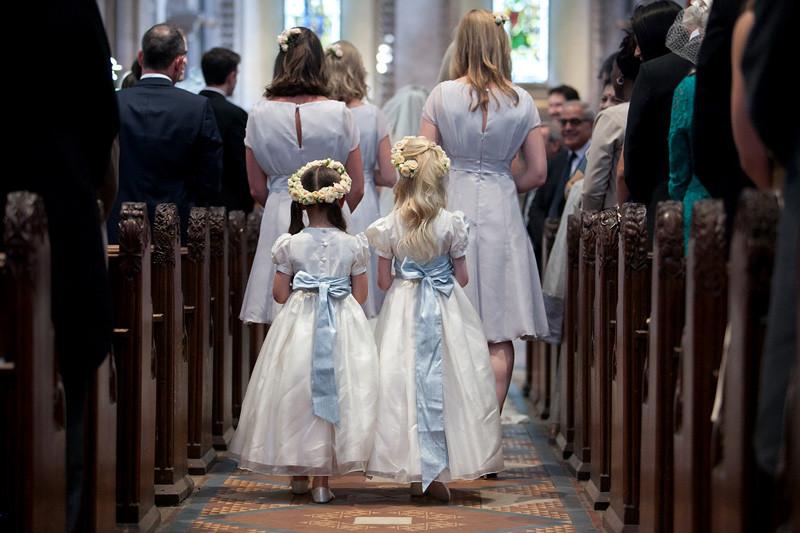 Bridebook.co.uk- flower girls walking behind bridesmaids