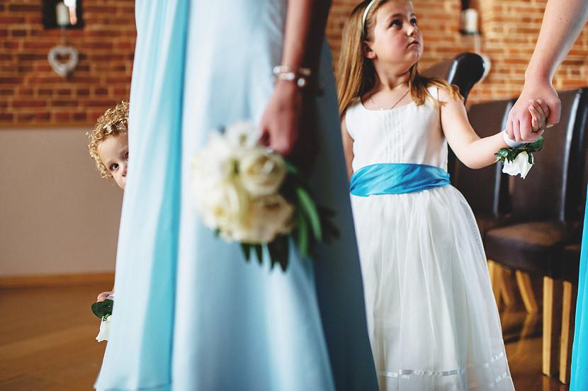 Bridebook.co.uk- flower girl peeking from behind bridesmaid