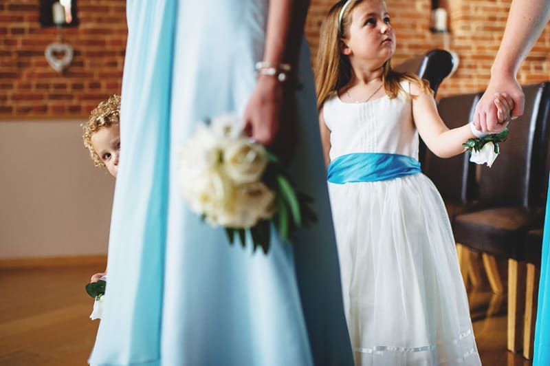 Bridebook.co.uk- flower girl peeking from behind bridesmaid