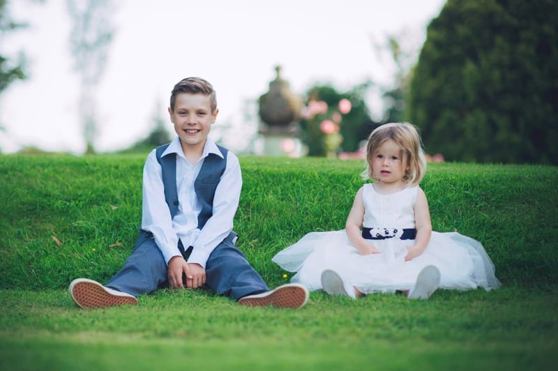 Bridebook.co.uk- page boy and flower girl sitting on grass