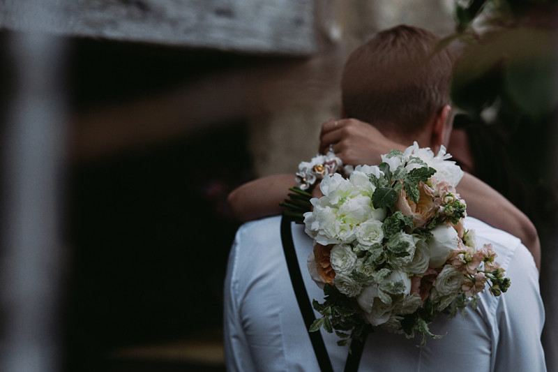 Bridebook.co.uk- bride hugging groom with the bouquet over his shoulder