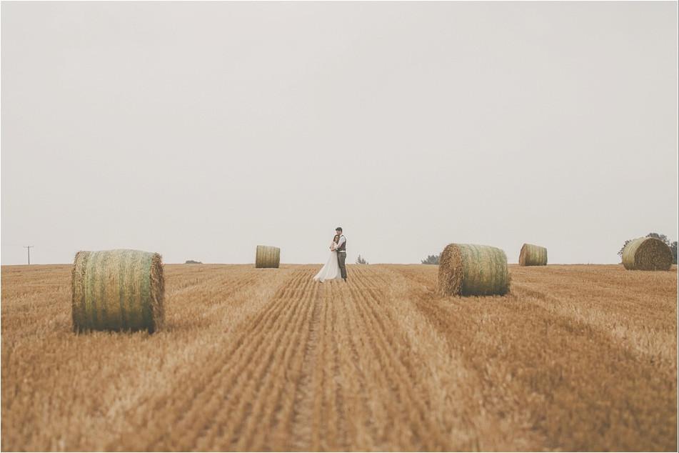 Bridebook.co.uk- bride and groom hugging in a field surrounded by hay bells