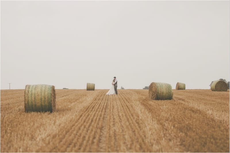Bridebook.co.uk- bride and groom hugging in a field surrounded by hay bells