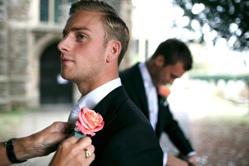 Bridebook.co.uk- groom getting the buttonnaire pinned to the lapel
