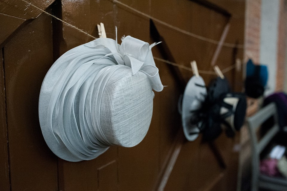 Bridebook.co.uk- ladies hats hanging up on pegs at reception