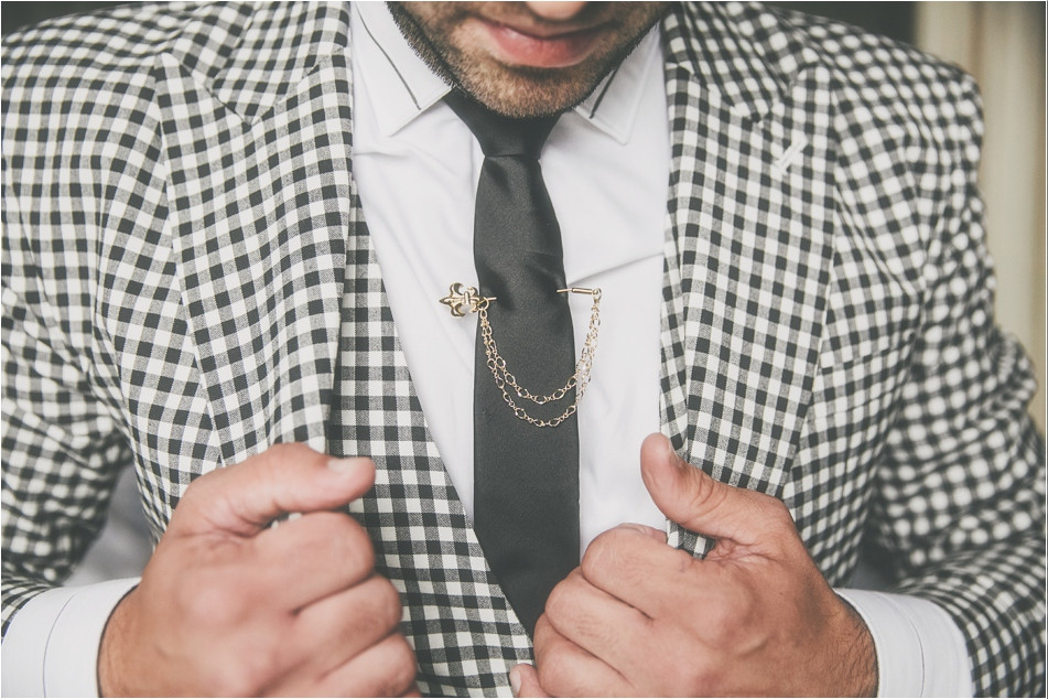 Bridebook.co.uk- groom in chequered suit with an ornate tie pin