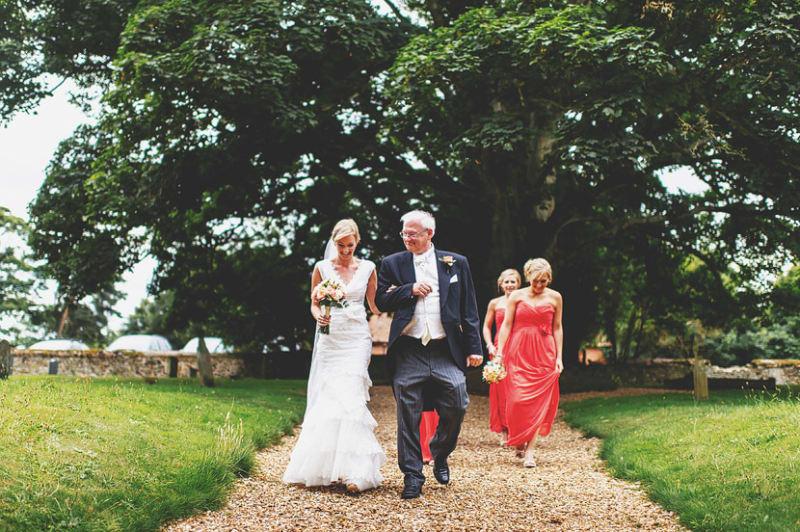 Bridebook.co.uk- bride father and bridesmaids walking to ceremony